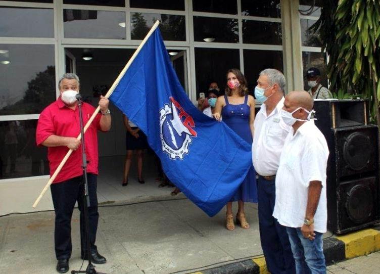Ulises, entrega bandera a Jorge Orestes, director y Pedro Suárez, secretario buró sindical