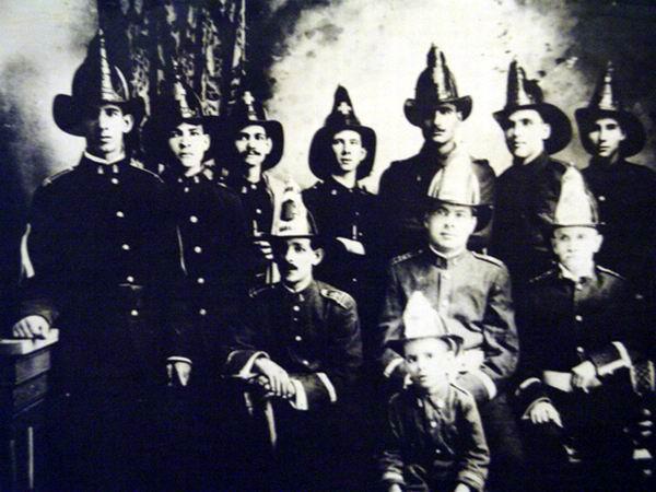 Grupo de bomberos con los trajes y cascos de la etapa colonial. Foto: Archivo del Cuerpo de Bomberos