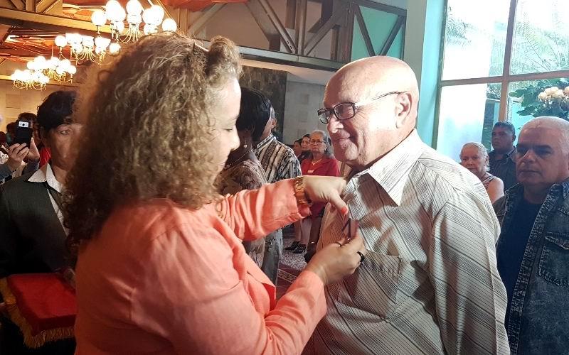 La integrante del Buró provincial del PCC, Damara Sánchez, impone la Orden Frank País, de Primer Grado, al maestro José Ángel Hernández