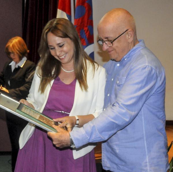 Milenis Torres (I), periodista del Sistema Informativo de la Televisión Cubana, recibe el Premio Anual de Periodismo