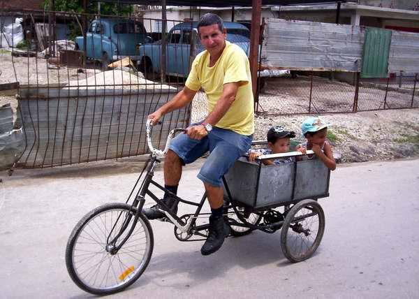 Papá paseando a sus dos pequeños en triciclo