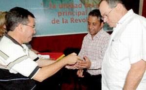 Julio César García, primer secretario del Partido y Luis Ynchausti, presidente del Poder Popular, entregan la réplica del Escudo de la provincia de Camagüey.