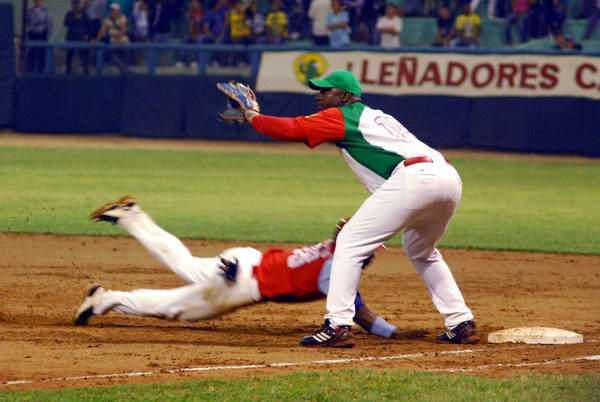 Los Leñadores (rojo y verde), de Las Tunas, y Los Tigres, de Ciego de Ávila, en el segundo juego de los play off de la 51 Serie Nacional de Béisbol, celebrado en el estadio Julio Antonio Mella, en Las Tunas, el 26 de abril de 2012. Foto: Yaciel Peña/AIN