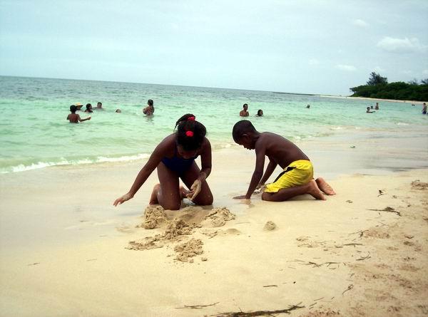 Niños se divierten jugando con la arena. Foto Abel Rojas