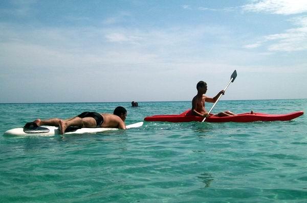 Bañistas disfrutan de la playa con kayak y tabla de surf. Foto Abel Rojas