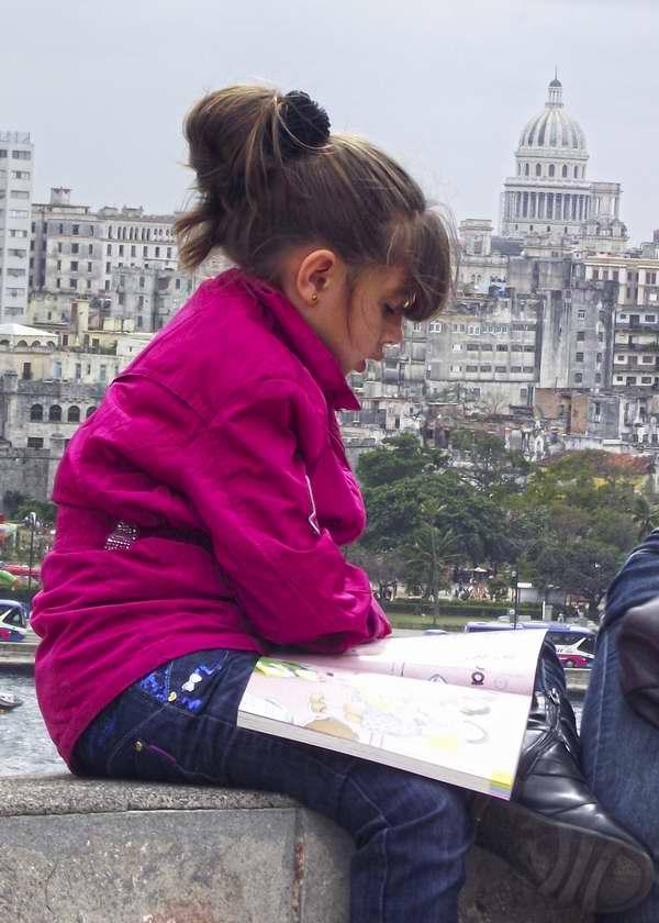 Pequeña lectora lee su libro en la sede permanente de la Feria del Libro. Foto Abel Rojas