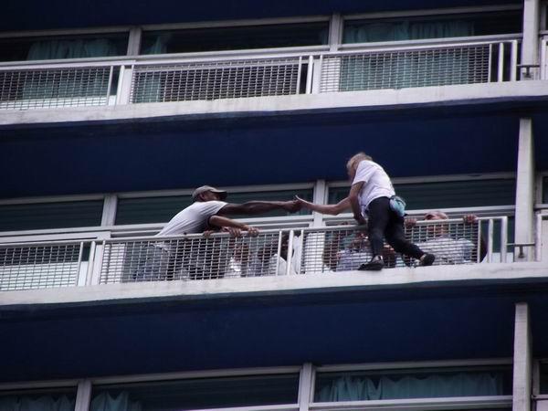El francés Alain Robert se toma un tiempo para saludar a su público durante la escalada del Hotel Habana Libre. Foto Abel Rojas