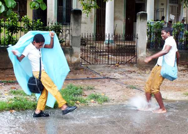 Niños se divierten bajo la lluvia. Foto Abel Rojas