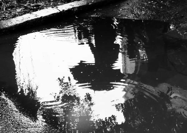 Imagen de persona con sombrilla reflejada en el agua estancada del pavimento. Foto Abel Rojas