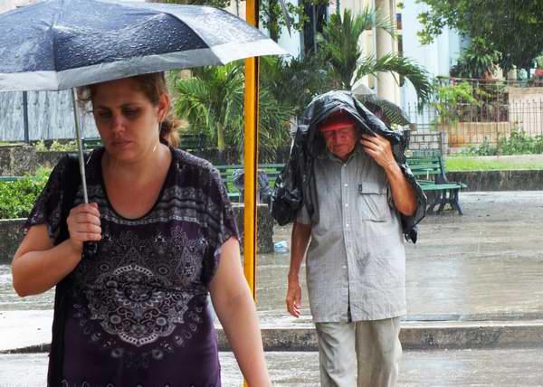 Personas protegiéndose de la lluvia. Foto Abel Rojas