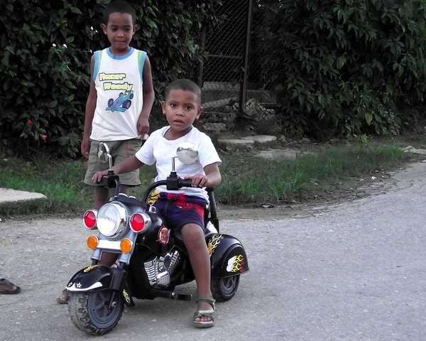 Un niño cubano disfruta con su moto de juguete. Foto Abel Rojas