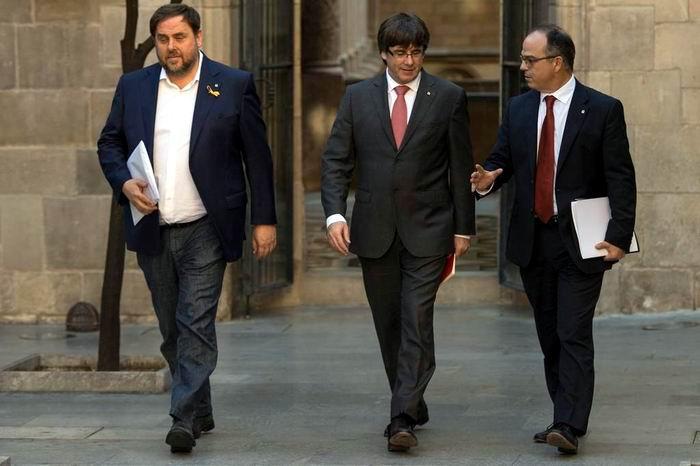 Carles Puigdemont (centro), su vice Oriol Junqueras (izq.) y su vocero Jordi Turull, en Barcelona. Foto: AFP